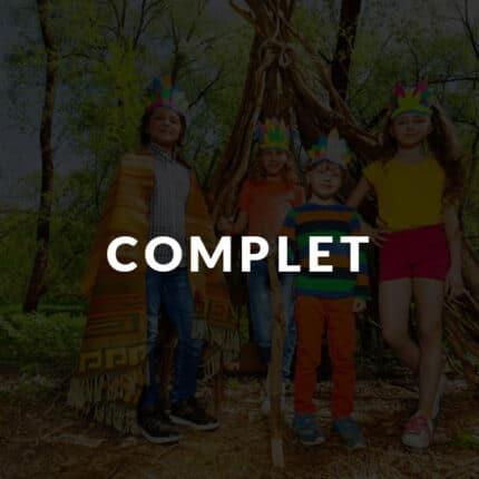 Quatre enfants dans une foret portent des costumes d'indiens en colonie de vacances