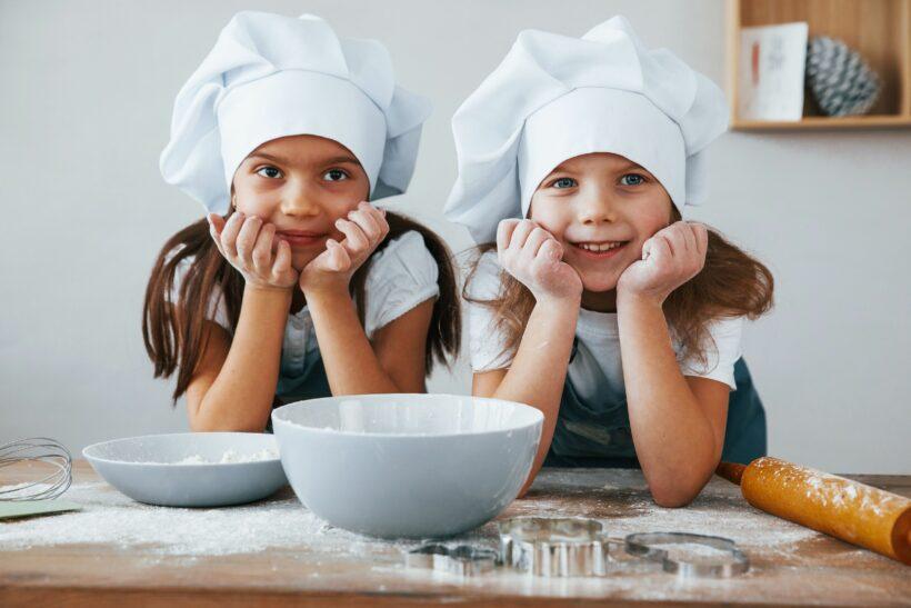 Deux petites filles font de la cuisine en colonie de vacances