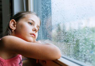 Enfant triste regarde par la fenêtre